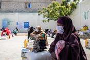 Internally displaced people collect food aid at an Islamic relief distr