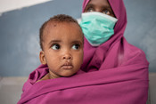 A mother holds her child at a health clinic in the Bondhere district of Mogadishu