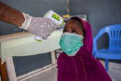 A member of the medical staff takes the temperature of a beneficiary in a health clinic in Mogadishu