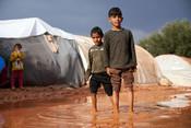 Brothers Jamal* (7), left, and Qasim* (10), right, walk through the mud in Zaitoun Maarshurin refugee camp