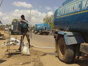 Clean water distributor Robert Hasfaman fills the handwashing stations